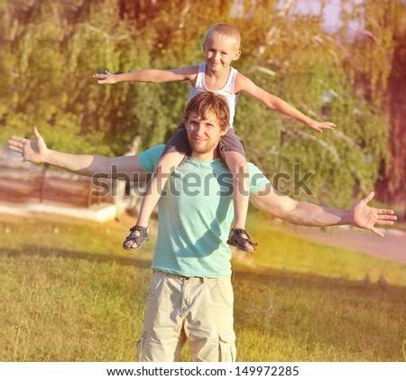 Family Father Man and Son Boy sitting on shoulders playing Outdoor park Happiness emotion with summer nature on background - stock photo