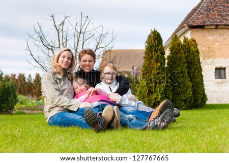Family, father, mother and daughters, sitting together on a meadow, they laugh and have fun - stock photo