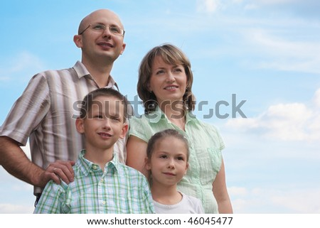family. father, mother, little boy and girl on sky background. - stock photo