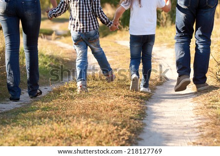 Family feet and legs in jeans. Father, mother, son and daughter walking on the road. Rear view. - stock photo