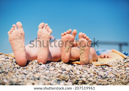 Family feet on beach background. Mother and son - stock photo