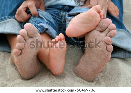 Family feet on sand. Mother and nine months old baby on beach.