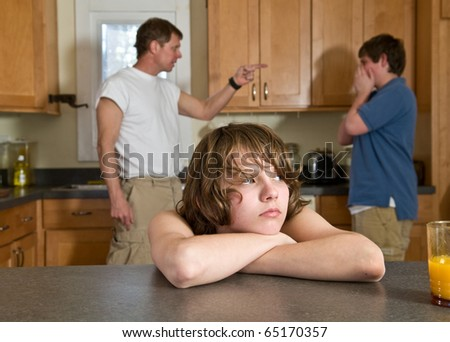 family fight - father scolds son as younger brother feels sad in foreground