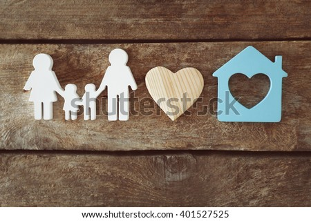 Family figure with a house on wooden  background - stock photo