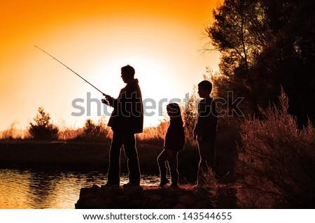 family fishing sunrise - stock photo