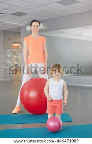 family, fitness, sport, training and lifestyle concept - smiling women and baby with exercise balls in gym