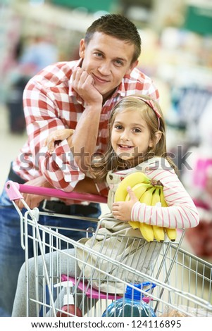 Family food shopping. Young man father and little girl daughter on trolley cart in supermarket - stock photo