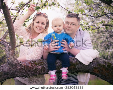 Family for a walk in the lush garden or the park in spring sunny day - stock photo