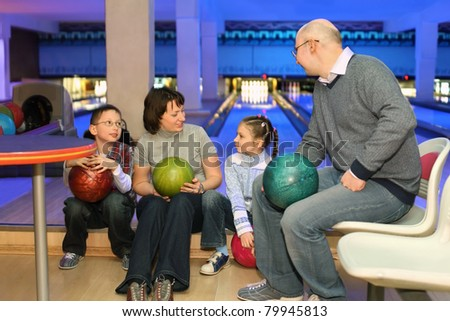 Family from four persons in rest and communicate in bowling club - stock photo