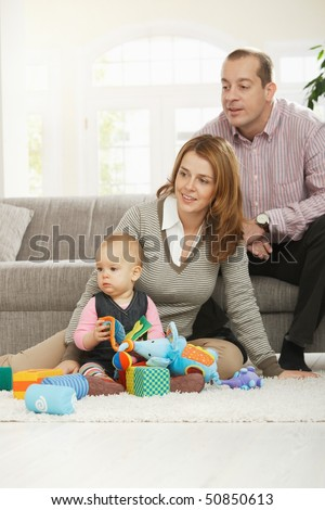 Family fun - Dad, mum and baby daughter playing with toys at home. - stock photo