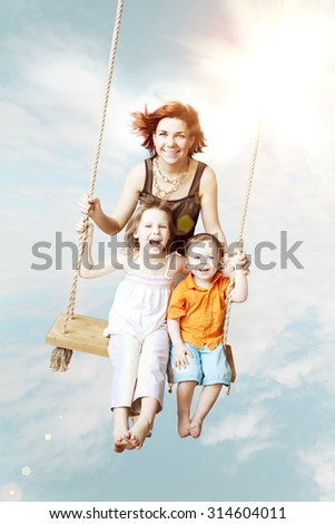 Family fun. Mom, daughter, son laughing on a swing against the sky and clouds. Family weekend vacation. - stock photo