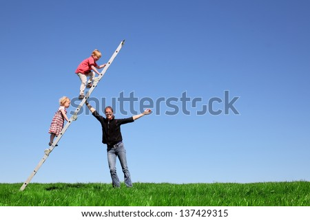 Family fun on green meadow and blue sky - stock photo
