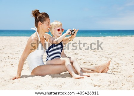 Family fun on white sand. Happy mother and daughter in swimsuits taking photos with digital camera at sandy beach on a sunny day
