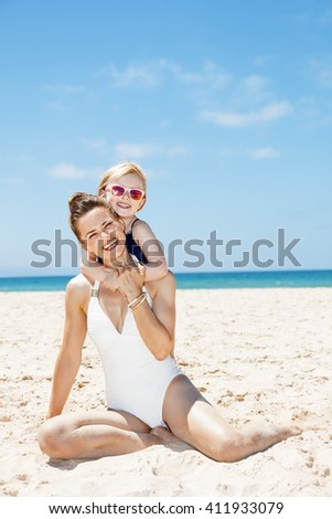 Family fun on white sand. Portrait of happy mother and child in swimsuits at sandy beach on a sunny day - stock photo