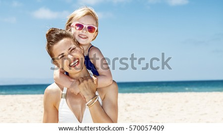 Family fun on white sand. Portrait of happy mother and child in swimsuits at sandy beach on a sunny day