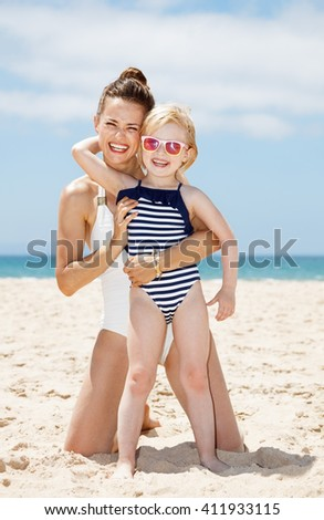 Family fun on white sand. Portrait of happy mother and child in swimsuits hugging at sandy beach on a sunny day