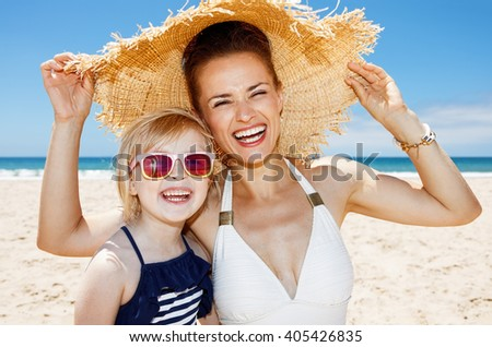 Family fun on white sand. Portrait of smiling mother and daughter under big straw hat at sandy beach on a sunny day - stock photo
