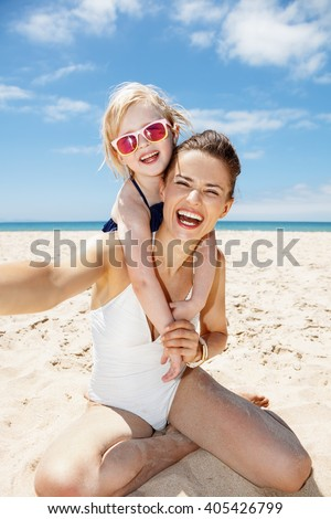 Family fun on white sand. Smiling mother and daughter in swimsuits taking selfies at sandy beach on a sunny day - stock photo