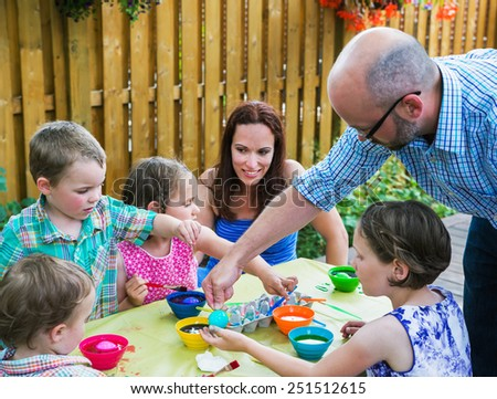 Family fun painting and decorating eggs outside during the spring season in a garden setting.  Father helps his children color dye their Easter eggs as the mother watches on.  Part of a series.    - stock photo