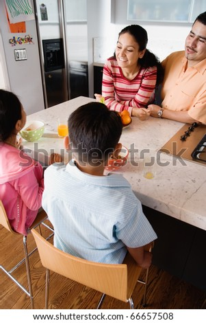 Family gathered around kitchen counter - stock photo