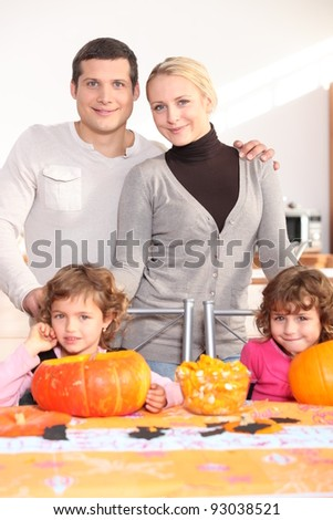 Family gathered around kitchen table preparing pumpkins - stock photo