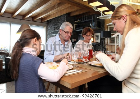 Family gathered around table - stock photo