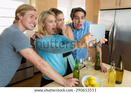 Family gathered to watch a sports game on TV tablet streaming video excited and celebrating - stock photo
