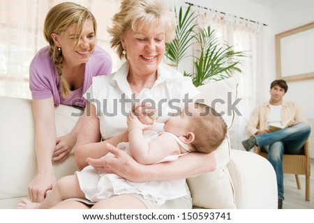 Family gathered together in their living room at home, relaxing and having the grandmother enjoying the feeding of a new baby girl and feeling proud, interior. - stock photo