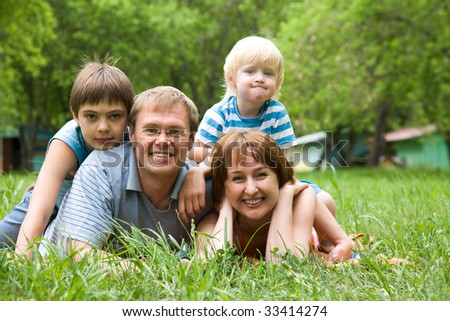 Family gathered together looking at camera - stock photo