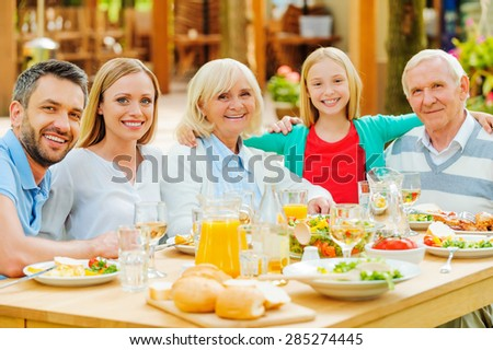 Family gathering. Happy family of five people bonding to each other and smiling while sitting at the dining table outdoors  - stock photo
