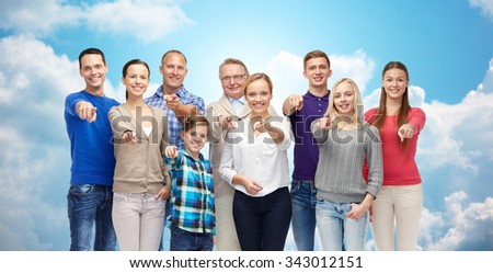 family, gender, generation and gesture concept - group of happy people pointing finger on you over blue sky and clouds background - stock photo