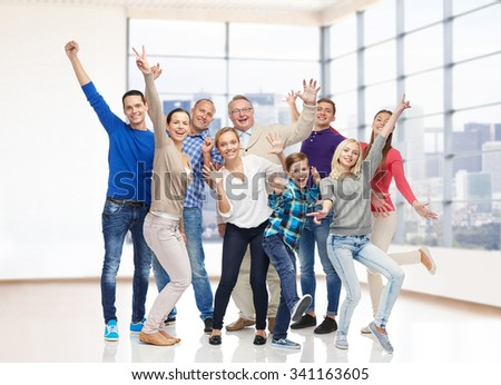 family, gender, generation and people concept - group of happy men, women and boy having fun and waving hands over empty office room or home - stock photo