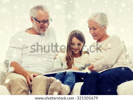 family, generation, education and people concept - smiling grandfather, granddaughter and grandmother with book or photo album sitting on couch at home - stock photo