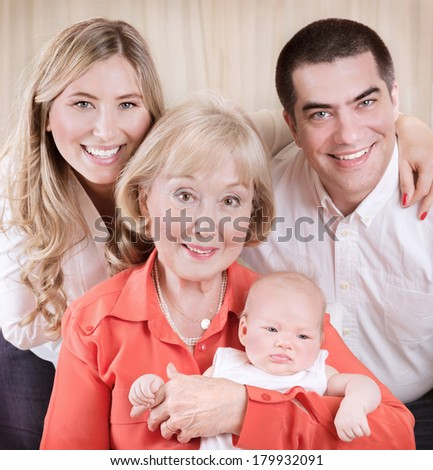 Family generation portrait, beautiful elegant grand mother holding on hands newborn granddaughter, mother and father standing behind them - stock photo
