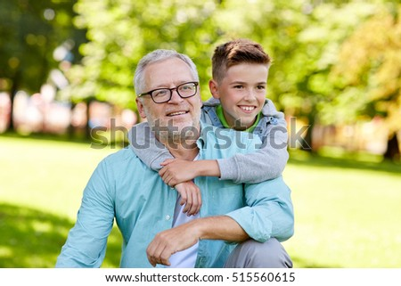 family, generation, relations and people concept - happy grandfather and grandson hugging at summer park
