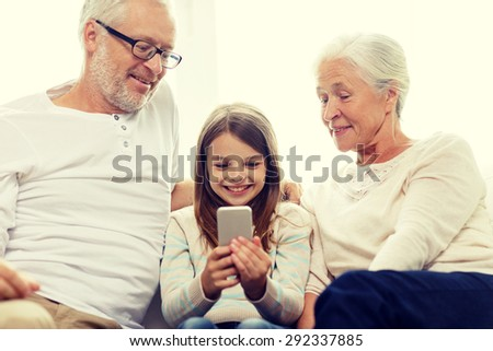 family, generation, technology and people concept - smiling grandfather, granddaughter and grandmother with smartphone sitting on couch at home - stock photo