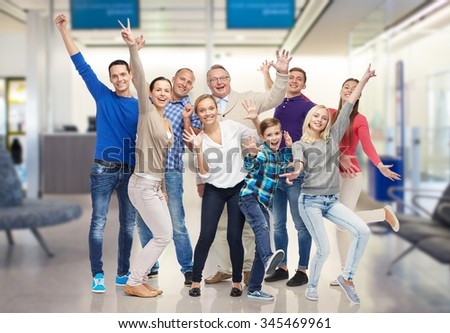 family, generation, travel, tourism and people concept - group of happy men, women and boy having fun and waving hands over airport waiting room background - stock photo