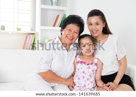 Family generations. Happy Asian family at home, grandparent, parent and grandchild sitting on sofa smiling looking at camera. - stock photo