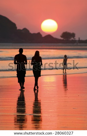 family goes for a walk on a beach on sunset - stock photo