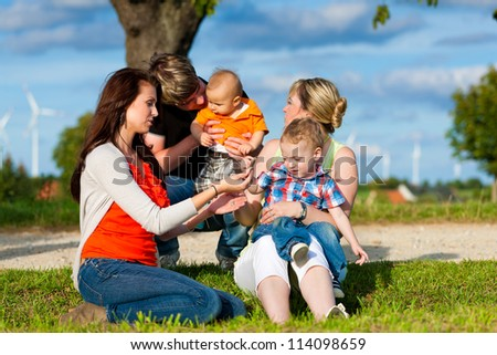 Family - Grandmother, mother, father and children sitting and playing in garden - stock photo