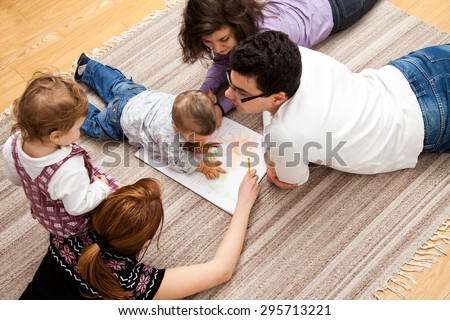 family group of five - two babies and three adults lying on the carpet, drawing a picture together. - stock photo