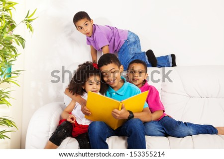 Family, group of four kids with older brother reading books to brothers and sister