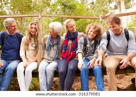 Family group sitting on a small bridge in a forest - stock photo