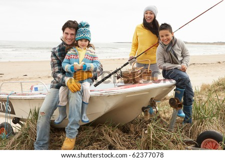 Family Group Sitting On Boat With Fishing Rod On Winter Beach - stock photo