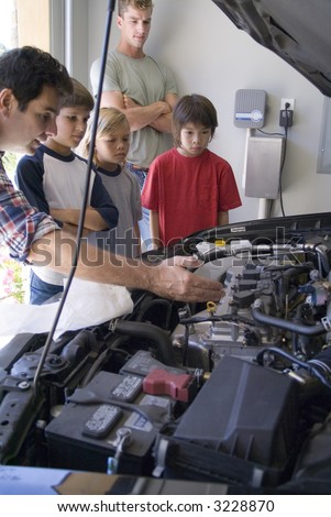 Family guys working on car - stock photo