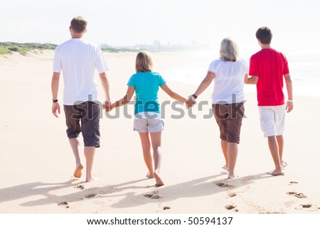 family hand in hand walking on beach