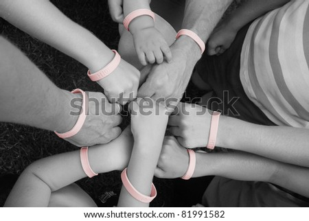 family hands with pink bracelets for breast cancer - stock photo
