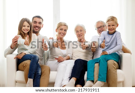 family, happiness, generation and people concept - happy family sitting on couch and showing thumbs up gesture at home - stock photo