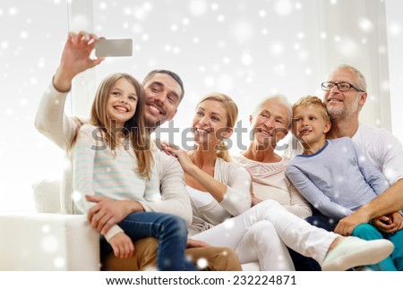 family, happiness, generation and people concept - happy family sitting on couch and taking selfie with smartphone at home