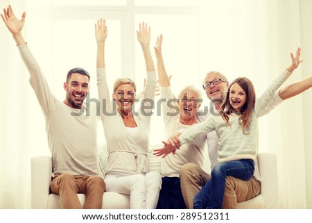 family, happiness, generation and people concept - happy family sitting on sofa and rising hands at home - stock photo